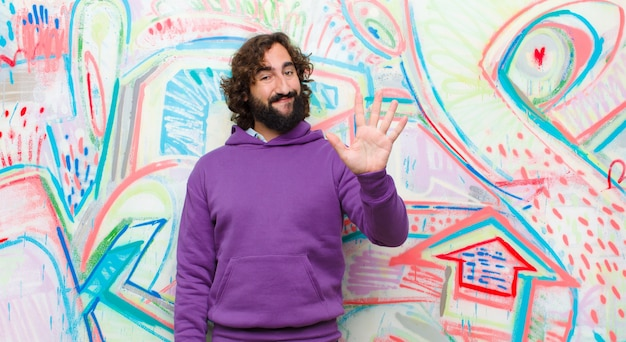 Young bearded crazy man smiling and looking friendly, showing number five or fifth with hand forward, counting down on graffiti wall