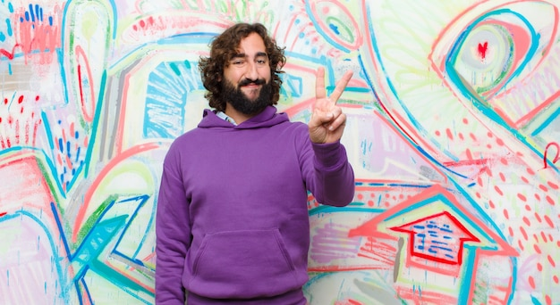 Young bearded crazy man smiling and looking friendly, showing number two or second with hand forward, counting down against graffiti