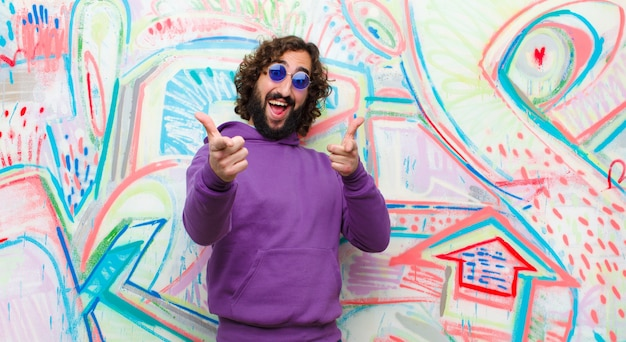 Young bearded crazy man smiling with a positive, successful, happy attitude pointing to the camera, making gun sign with hands against graffiti