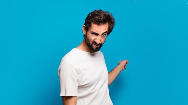 コピースペースを持つ若いひげを生やした狂った男。怒りの表情