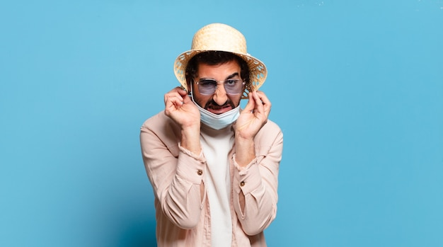 Молодой бородатый сумасшедший с маской covid. концепция путешествия.