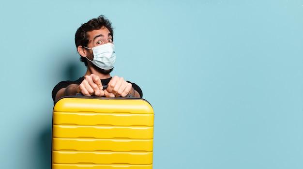 Covid 保護マスクをした若いひげを生やした狂人。旅行のコンセプト