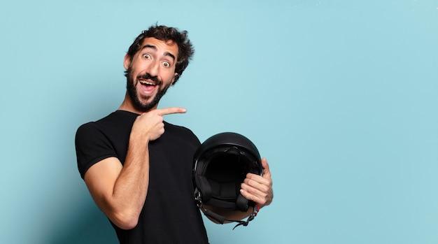 バイクのヘルメットを持つ若いひげを生やした狂った男