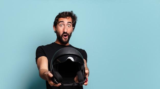 バイクのヘルメットを持つ若いひげを生やした狂気の男
