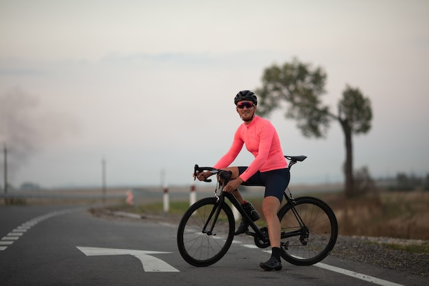 Young bearded cyclist on bright clothing,helmet and glasses smiling while sitting on his bike outdoors