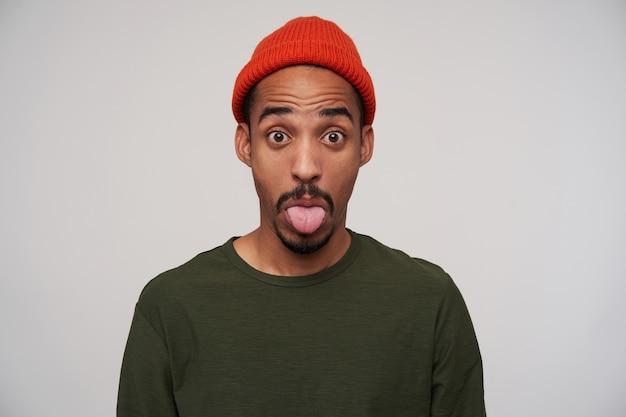 Giovane uomo dalla pelle scura con la barba che alza sorpreso sopracciglia e mostra la sua lingua, prendendo in giro mentre posa su bianco