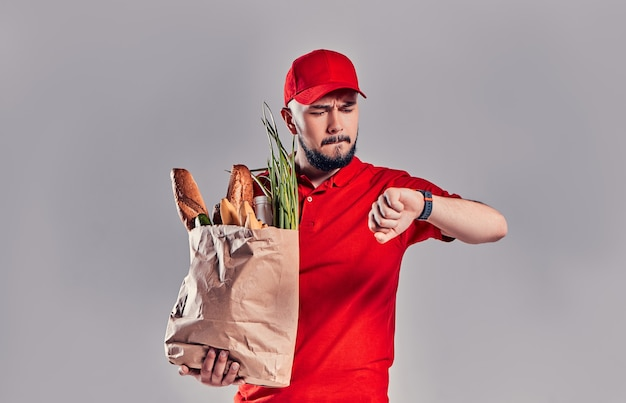 赤い制服を着た若いひげを生やした配達人は、パンと野菜のパッケージを保持し、灰色の背景に遅れて孤立している彼の手でスマートウォッチを見ています。