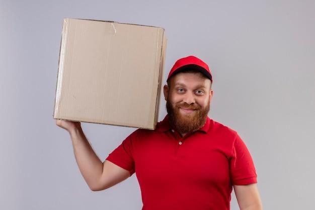 自信を持って笑顔でカメラを見ている赤い制服とキャップ保持段ボール箱の若いひげを生やした配達人