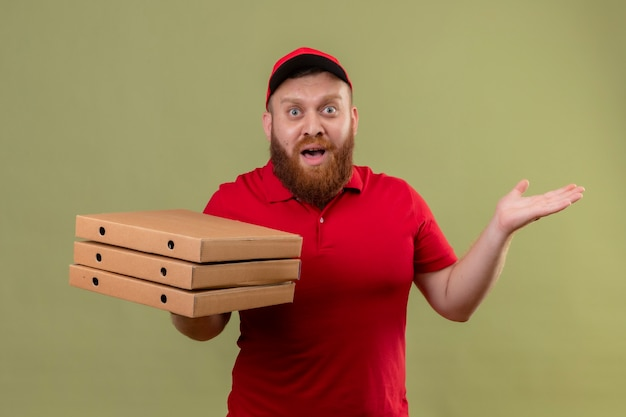 Молодой бородатый курьер в красной форме и кепке держит стопку коробок из-под пиццы, выглядит встревоженным и смущенным с поднятыми руками