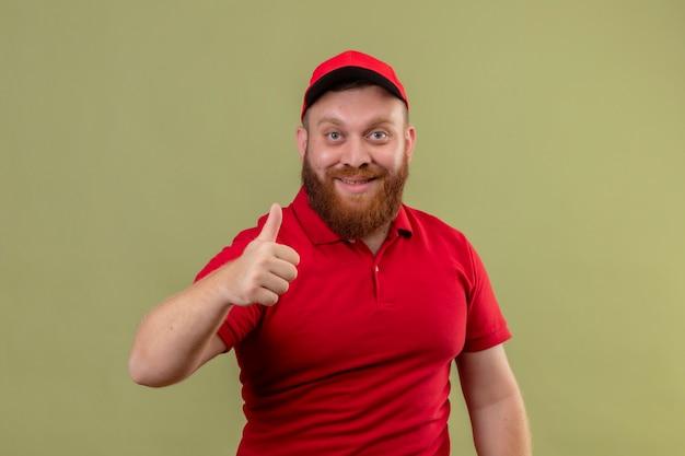 Молодой бородатый курьер в красной форме и кепке, весело улыбаясь, показывает палец вверх