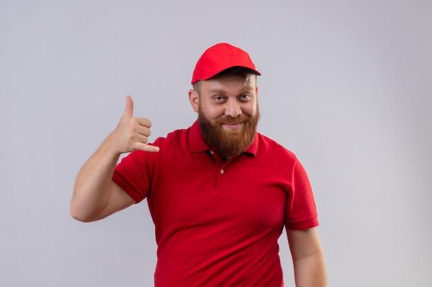 Молодой бородатый курьер в красной форме и кепке улыбается, делая жест рукой
