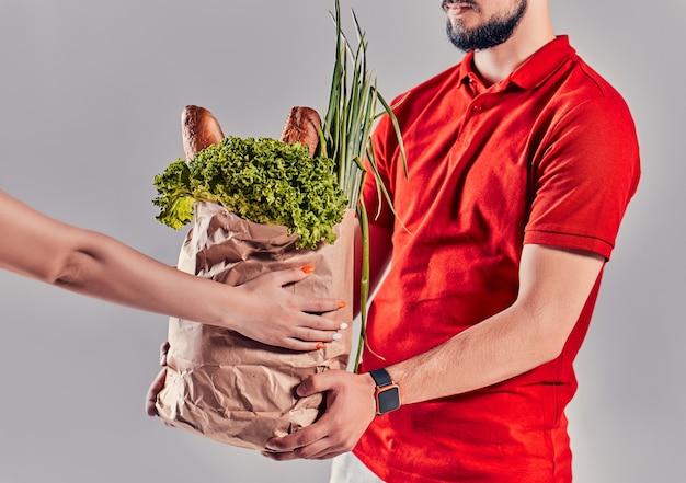 赤い制服を着た若いひげを生やした配達人は、灰色の背景で隔離のクライアントにパンと野菜のパッケージを配信します。
