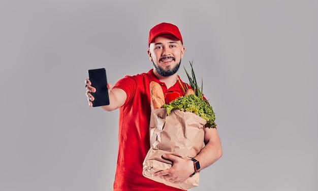 빨간 제복을 입은 수염난 배달원은 빵과 야채가 든 꾸러미를 들고 회색 배경에 격리된 스마트폰 화면을 보여줍니다.