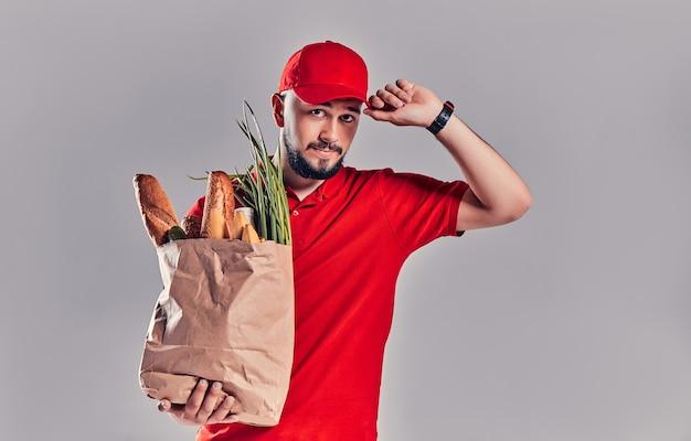 赤い制服を着た若いひげを生やした配達人は、灰色の背景に分離されたパンと野菜のパッケージを保持します。
