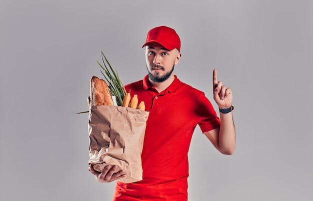 赤い制服を着た若いひげを生やした配達人は、灰色の背景に分離された親指を示すパンと野菜のパッケージを保持します。