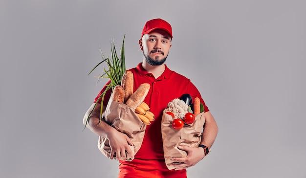 赤い制服を着た若いひげを生やした配達人は、灰色の背景に分離されたパンと野菜と2つの大きな重いパッケージを保持しています。