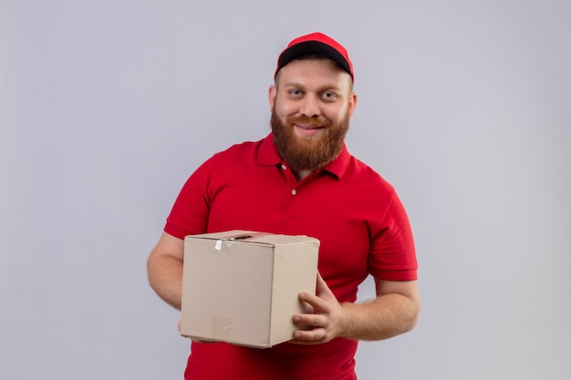 Young bearded delivery man in red uniform and cap holding cardboard box looking at camera with confident smile 2