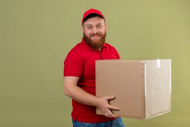 Giovane uomo di consegna barbuto in uniforme rossa e cappuccio che tiene la scatola di cartone che guarda l'obbiettivo con un sorriso fiducioso