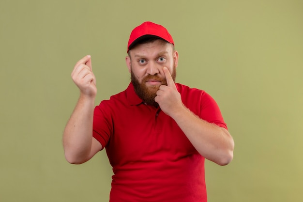 Giovane uomo di consegna barbuto in uniforme rossa e cappuccio che guarda l'obbiettivo che punta con il dito al suo occhio strofinando le dita facendo gesto di denaro, in attesa di pagamento