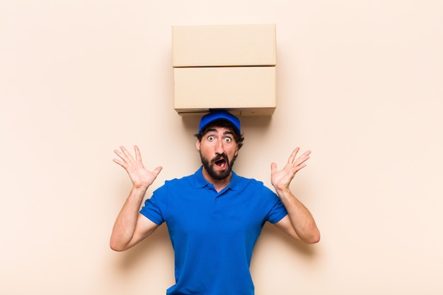 Young bearded delivery man with a box feeling shocked