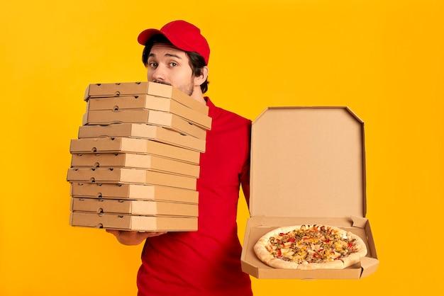 Молодой бородатый курьер с изолированными коробками пиццы. доставка на дом.