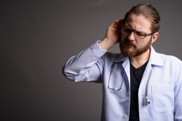 Young bearded doctor against gray wall