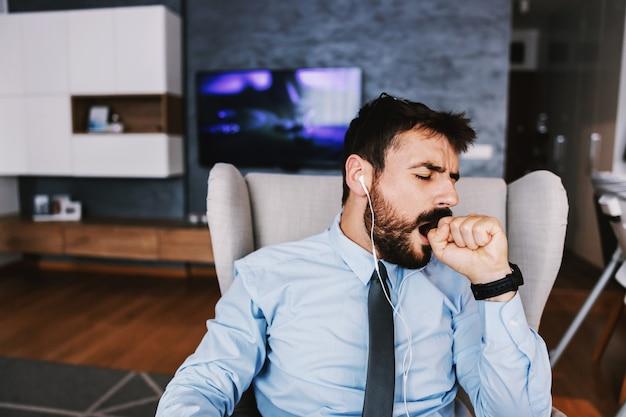 若いひげを生やした従業員は、家に座ってあくびをしているエレガントな服を着ています。 covid検疫の概念。