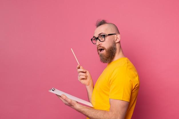 ピンクの背景にメモを取る若いひげを生やした従業員男性カジュアルウェア