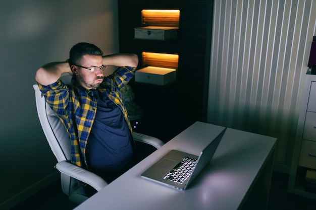 Young bearded employee with eyeglasses trying to solve problem while looking at laptop