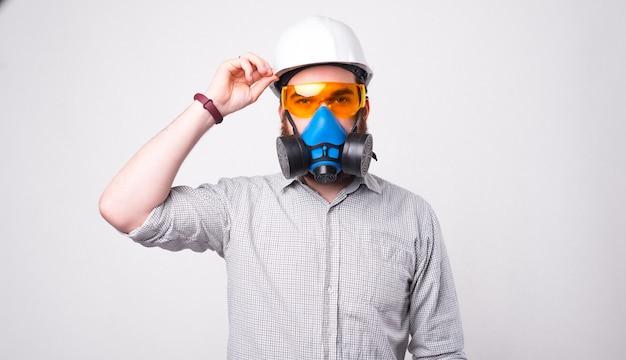 ヘルメット、保護メガネ、呼吸器を身に着けている若いひげを生やしたエンジニアは、白い壁の近くでカメラを見ています