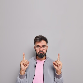 Young bearded european man points index fingers above shows something