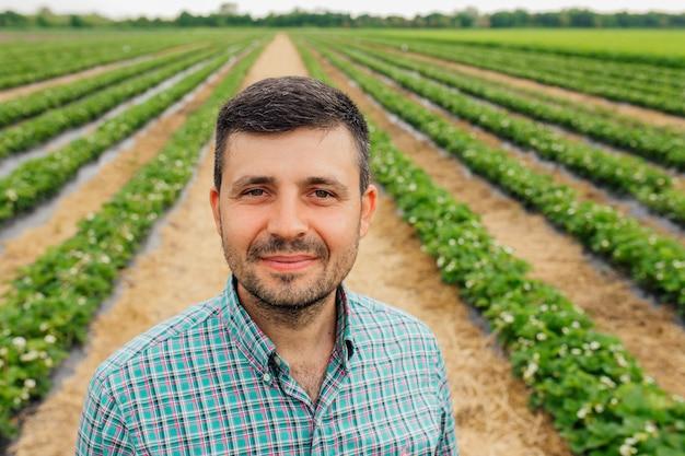 Молодой бородатый фермер европейской национальности смотрит в камеру и улыбается мужчина-фермер, одетый в рубашку с квадратами, находится на сельскохозяйственном поле