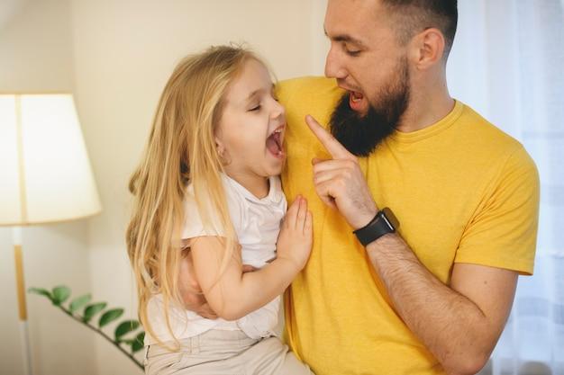 젊은 수염 된 아버지는 아침에 집에서 그의 작은 딸과 함께 연주. 귀여운 금발 소녀는 그녀의 아버지의 손가락을 물려고하는 동안 재미.
