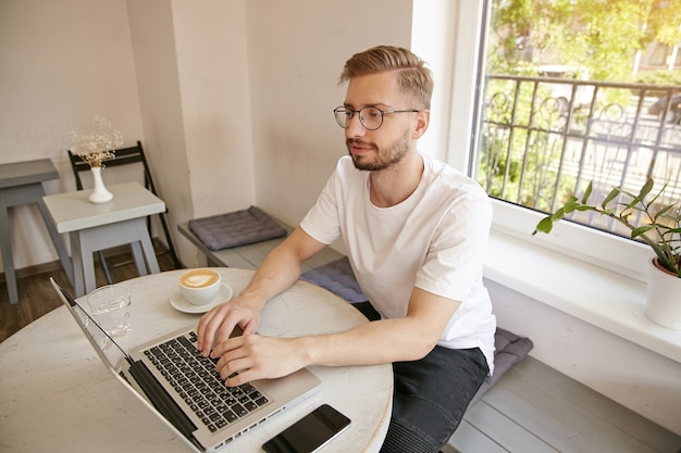 Young bearded freelancer wearing white t-shirt and glasses, sitting at table in coffee room and using laptop, checking emails and looking concentrated