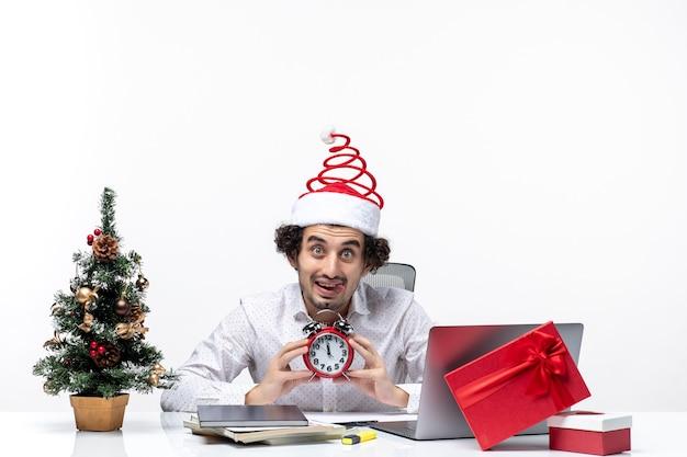 Giovane barbuto uomo d'affari divertente con cappello di babbo natale e mostrando orologio guardando qualcosa di sorpresa e seduto in ufficio su sfondo bianco