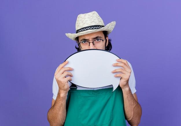 青い壁の上に立っている彼の顔を隠している空白の吹き出し看板を保持しているジャンプスーツと帽子を身に着けている若いひげを生やした庭師の男