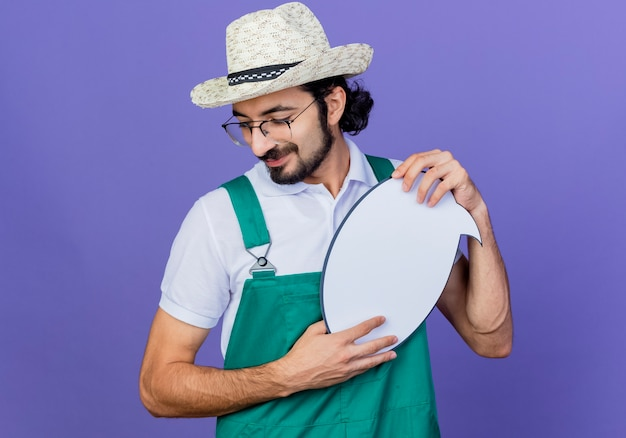 青い壁の上に立っている顔に笑顔で脇を見て空白の吹き出し看板を保持しているジャンプスーツと帽子を身に着けている若いひげを生やした庭師の男