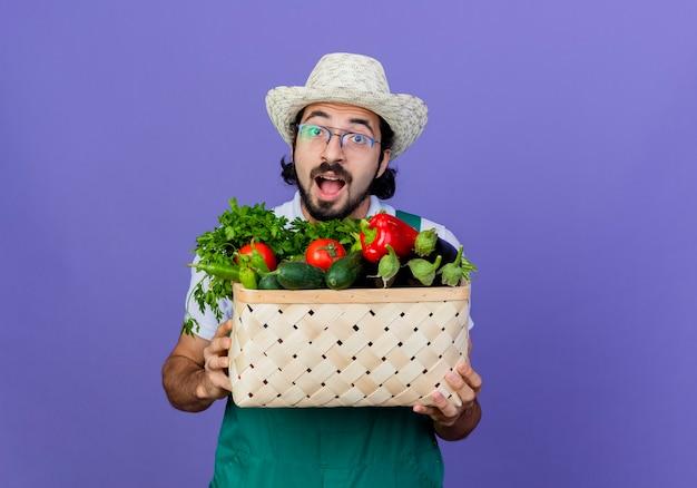 青い壁の上に立って幸せで興奮して正面を見て野菜でいっぱいの木枠を保持しているジャンプスーツと帽子を身に着けている若いひげを生やした庭師の男