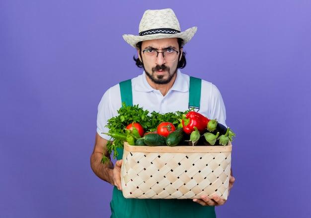 青い壁の上に立っている深刻な顔のしかめっ面で正面を見て野菜でいっぱいの木枠を保持しているジャンプスーツと帽子を身に着けている若いひげを生やした庭師の男