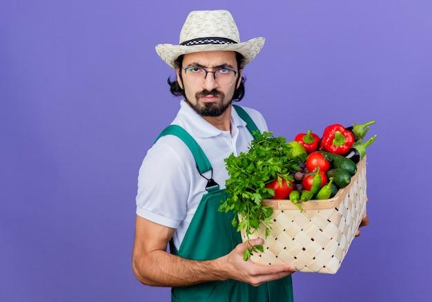青い壁の上に立っている深刻なしかめっ面で正面を見て野菜でいっぱいの木枠を保持しているジャンプスーツと帽子を身に着けている若いひげを生やした庭師の男