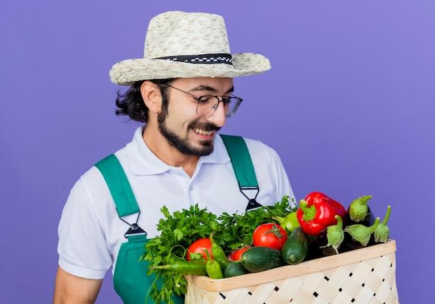青い壁の上に元気に立って笑っている野菜でいっぱいの木枠を保持しているジャンプスーツと帽子を身に着けている若いひげを生やした庭師の男