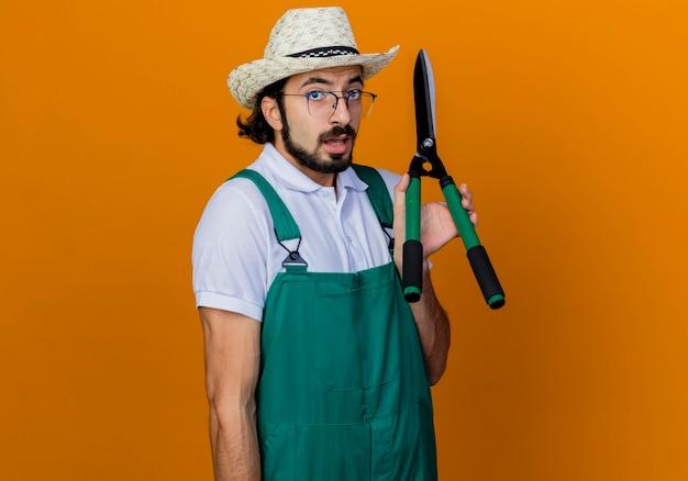 젊은 수염 정원사 남자 점프 슈트와 모자를 쓰고 헤지 클리퍼를 들고 정면을보고 혼란스러워하는 오렌지 벽 위에 서서