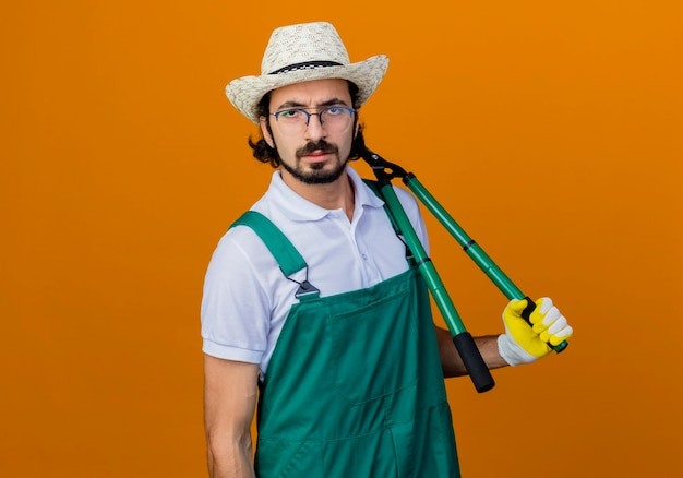 젊은 수염 정원사 남자 죄수 복과 오렌지 벽 위에 서 심각한 얼굴로 정면을보고 울타리 가위를 들고 모자를 쓰고