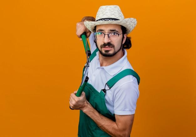 젊은 수염 정원사 남자 점프 슈트와 모자를 쓰고 울타리 가위를 들고 정면을보고 오렌지 벽 위에 서 걱정