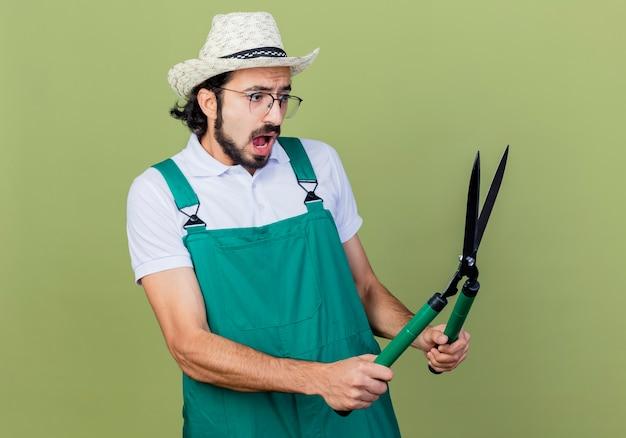 젊은 수염 정원사 남자 점프 슈트와 모자를 들고 헤지 클리퍼를 들고 놀라게하고 밝은 녹색 벽 위에 서서 혼란스러워합니다.