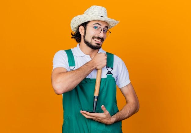 オレンジ色の壁の上に元気に立って笑顔の正面を見てミニ熊手を保持しているジャンプスーツと帽子を身に着けている若いひげを生やした庭師の男