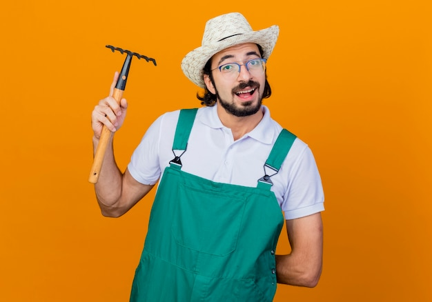 オレンジ色の壁の上にフレンドリーな立って笑顔の正面を見てミニ熊手を保持しているジャンプスーツと帽子を身に着けている若いひげを生やした庭師の男