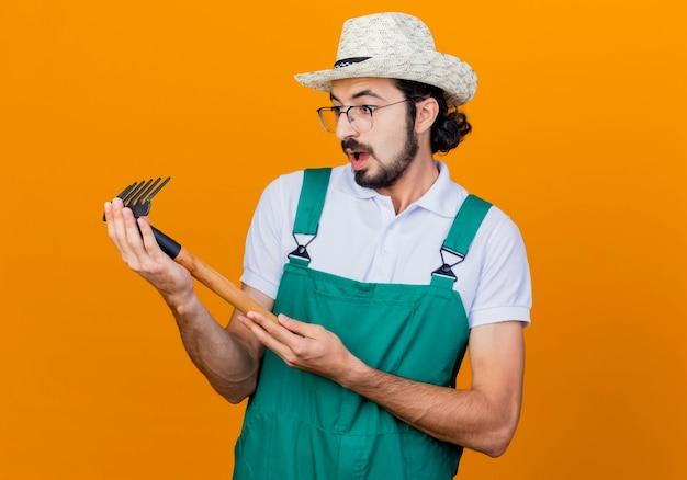 ジャンプスーツと帽子をかぶった若いひげを生やした庭師の男がオレンジ色の壁の上に立って驚いてそれを見てミニ熊手を保持