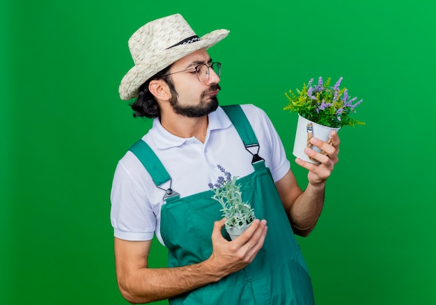 真面目な顔でそれらを見ている鉢植えの植物を保持しているジャンプスーツと帽子を身に着けている若いひげを生やした庭師の男