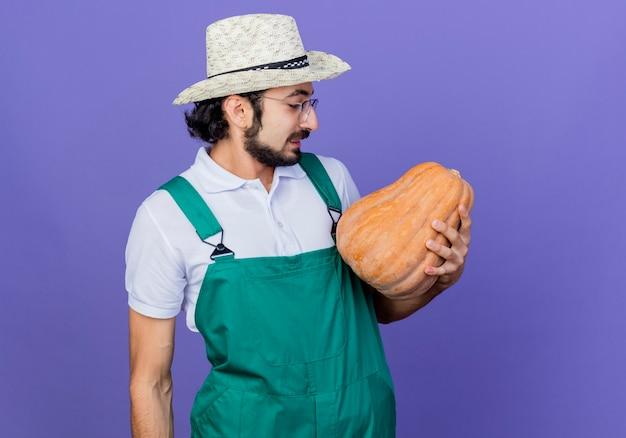 Молодой бородатый садовник в комбинезоне и шляпе держит тыкву, глядя на нее, улыбаясь, стоя у синей стены